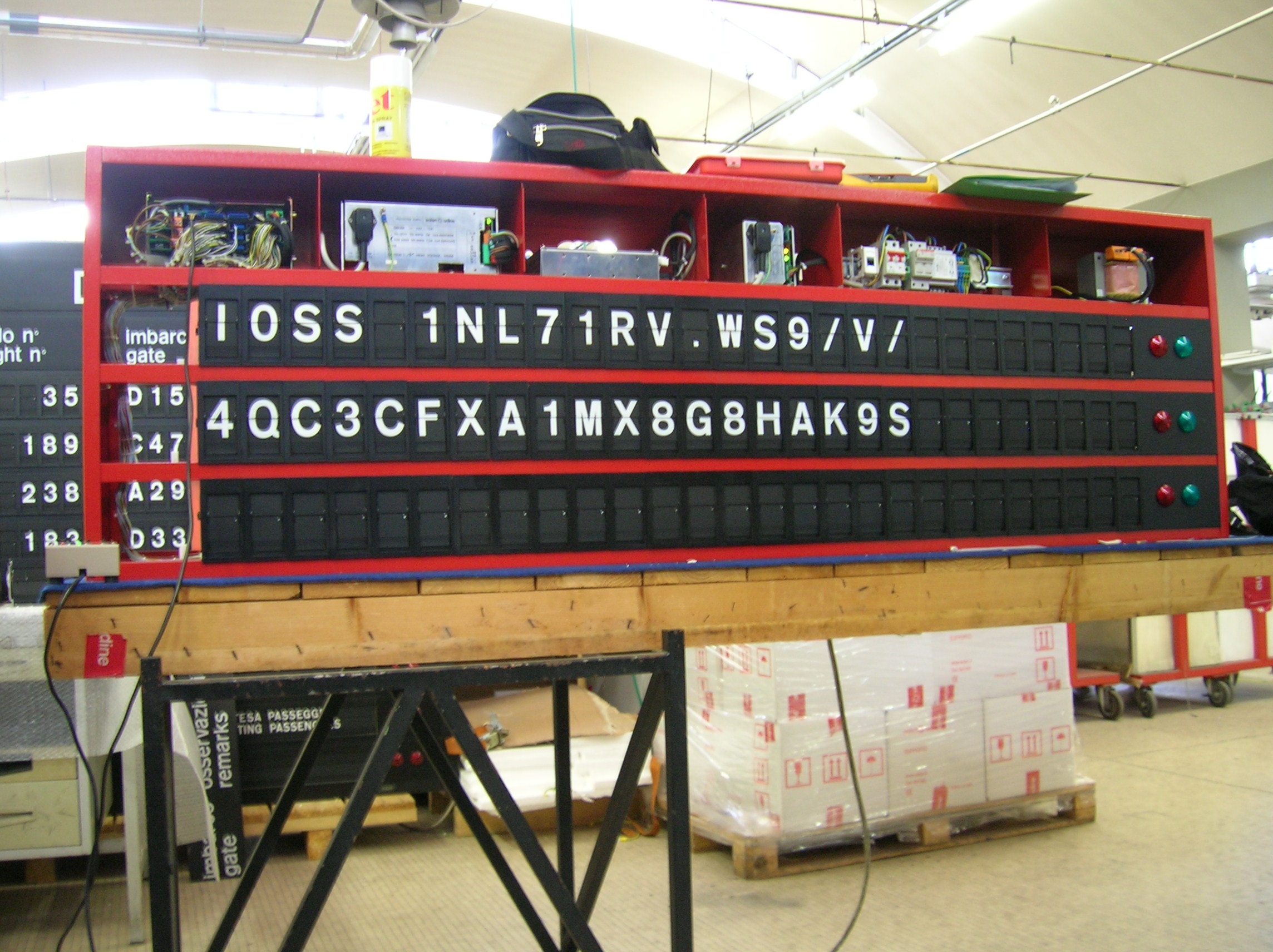 Image of large bright red three-line Solari split-flap board. Above the 432bee4339